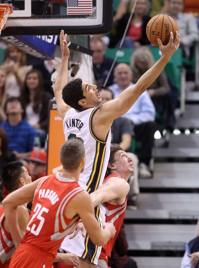 Enes Kanter, center, of Turkey, pulls down a rebound as Omer Asik, left, of Turkey, and teammate Chandler Parsons (25) defend. Photo: Rick Bowmer, Associated Press
