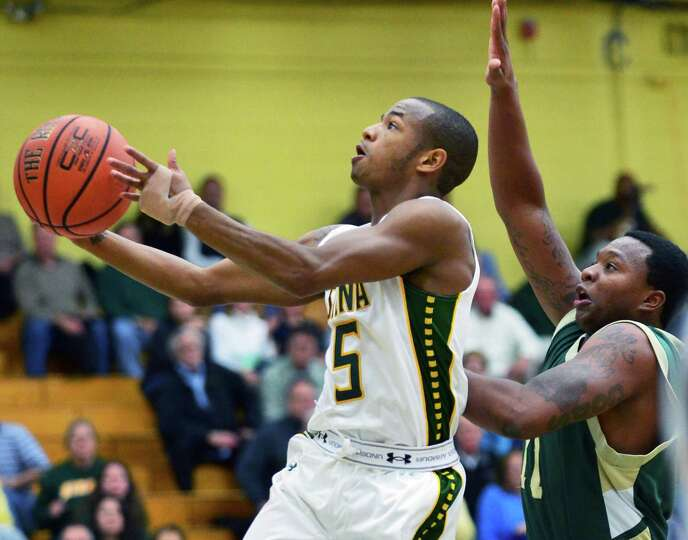 Siena's #5 Evan Hymes, left, gets past New Jersey City University's 11 Khalid Muhammad to go to the