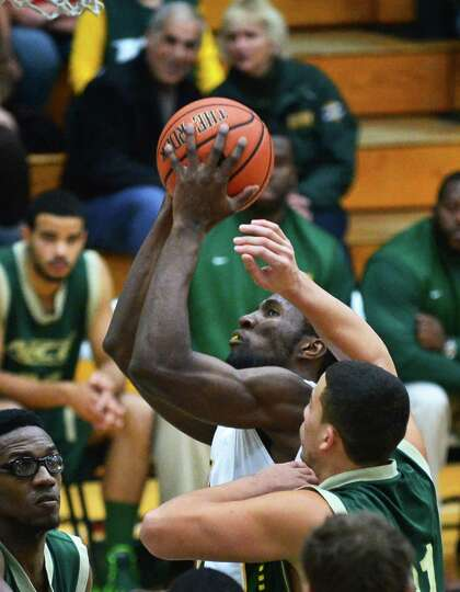 Siena's #34 Imoh Silas, center, gets a shot through New Jersey City University's defense during an e
