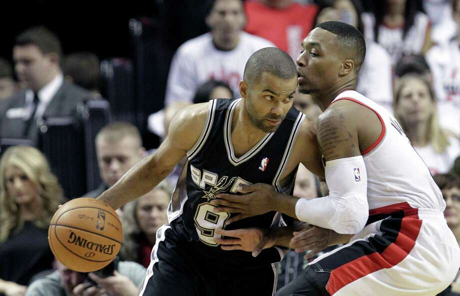 San Antonio Spurs guard Tony Parker, left, drives on Portland Trail Blazers guard Damian Lillard during the first half of an NBA basketball game in Portland, Ore., Saturday, Nov. 2, 2013. (AP Photo/Don Ryan) Photo: Don Ryan, Associated Press / AP