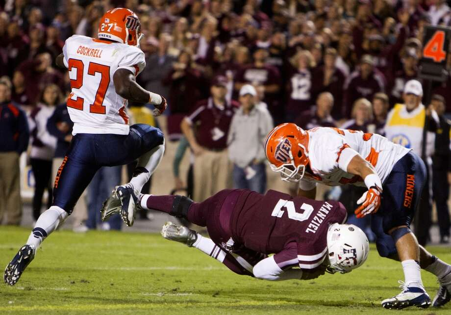Texas A&M Aggies quarterback Johnny Manziel dives between UTEP Miners defensive back Devin Cockrell, left, and linebacker Anthony Puente, right, for a touchdown during the first half of an NCAA college football game at Kyle Field Saturday, Nov. 2, 2013, in College Station. (Cody Duty / Houston Chronicle) Photo: Cody Duty, Houston Chronicle