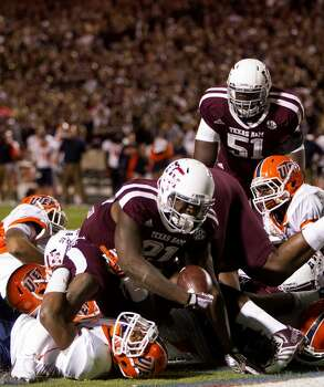 Texas A&M Aggies running back Tra Carson dives over the line for a touchdown during the second quarter of an NCAA college football game against the UTEP Miners at Kyle Field Saturday, Nov. 2, 2013, in College Station. (Cody Duty / Houston Chronicle) Photo: Cody Duty, Houston Chronicle