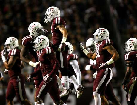 Texas A&M Aggies defensive back Noel Ellis, center, leaps into the air as the Aggies celebrate a fumble recovery from UTEP Miners wide receiver Jordan Leslie during the second quarter of an NCAA college football game at Kyle Field Saturday, Nov. 2, 2013, in College Station. (Cody Duty / Houston Chronicle) Photo: Cody Duty, Houston Chronicle