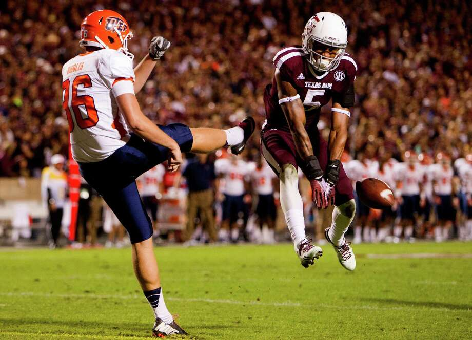 Before piling on the points via touchdowns, the Aggies started in a slow but acrobatic fashion as Floyd Raven, right, blocks a punt by UTEP's Mike Ruggles for a safety during the first quarter Saturday night at Kyle Field. Photo: Cody Duty, Staff / © 2013 Houston Chronicle