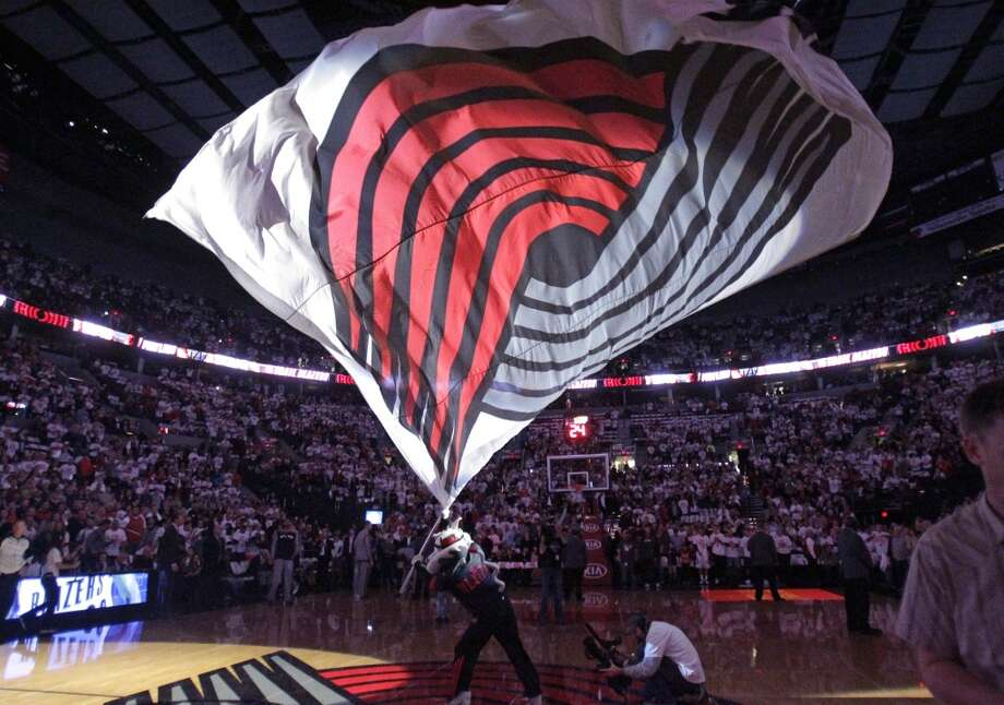 Portland Trail Blazers mascot Blaze waves the team flag for the NBA basketball team's home-opener against the San Antonio Spurs in Portland, Ore., Saturday, Nov. 2, 2013. Photo: Don Ryan, Associated Press