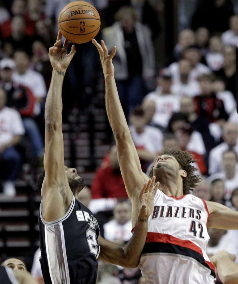 San Antonio Spurs forward Tim Duncan, left, shoots over Portland Trail Blazers center Robin Lopez during the first half of an NBA basketball game in Portland, Ore., Saturday, Nov. 2, 2013. Photo: Don Ryan, Associated Press