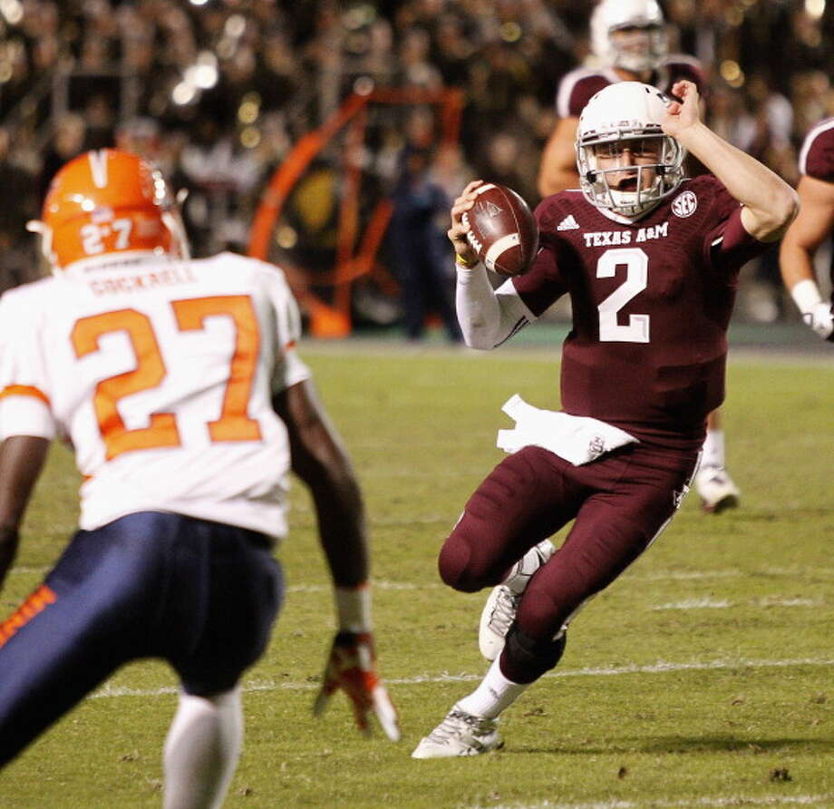 Johnny Manziel #2 of the Texas A&M Aggies runs with the ball in the second quarter as defensive back Devin Cockrell #27 of the UTEP Miners looks to make a tackle at Kyle Field on November 2, 2013 in College Station, Texas. Photo: Bob Levey, Getty Images / 2013 Getty Images