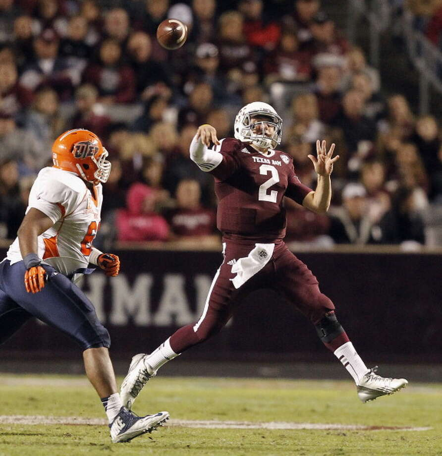 Johnny Manziel #2 of the Texas A&M Aggies throws on the run as he is pursued by Germard Reed #61 of the UTEP Miners at Kyle Field on November 2, 2013 in College Station, Texas. Photo: Bob Levey, Getty Images / 2013 Getty Images