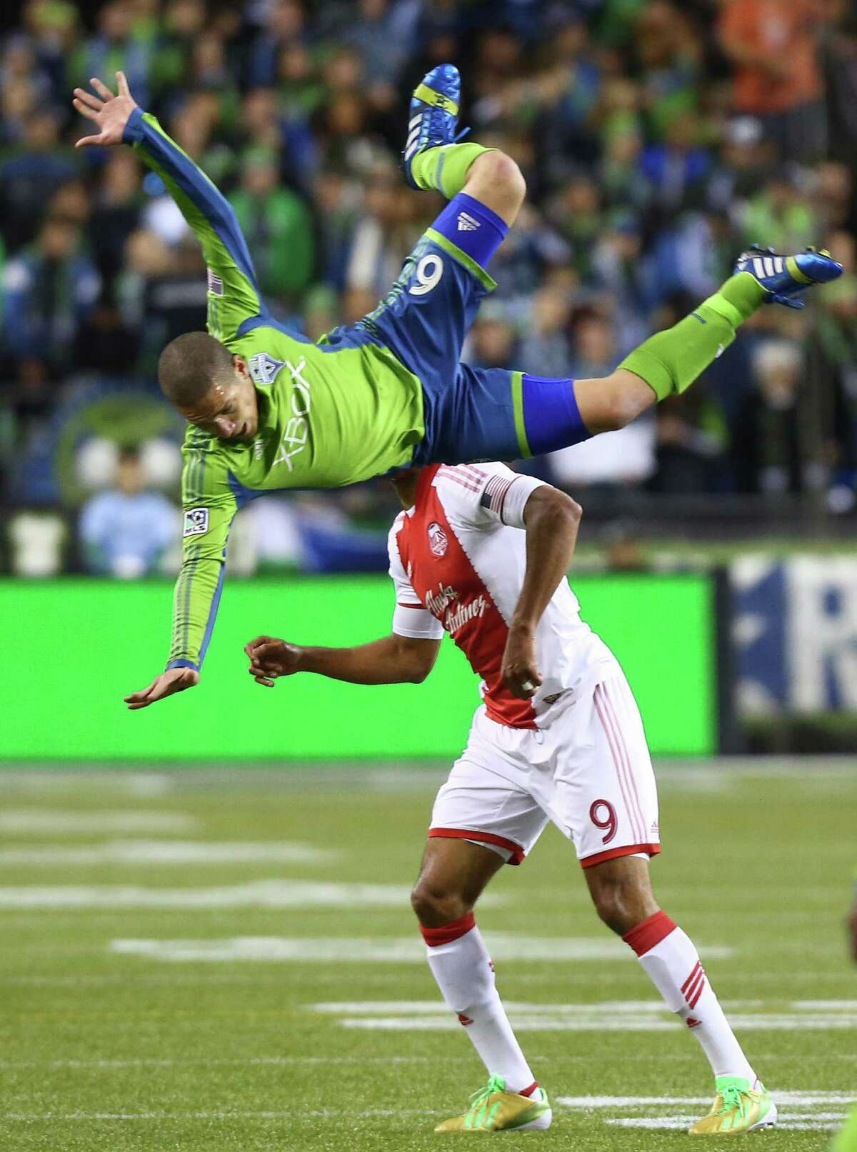 Seattle Sounders player Osvaldo Alonso is upended by Portland Timbers player Ryan Johnson during an MLS playoff match between the two Pacific Northwest rivals. The Sounders fell to the Timbers 2-1.