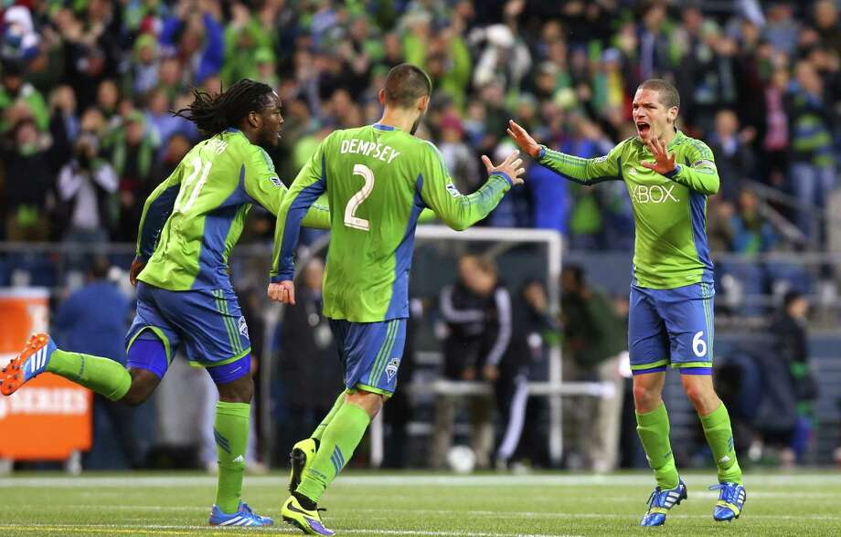 Seattle Sounders player Osvaldo Alonso reacts with teammates Clint Dempsey and Shalrie Joseph after Alonso scored a goal late in the game against the Portland Timbers during an MLS playoff match between the two Pacific Northwest rivals. The Sounders fell to the Timbers 2-1.  Photo: JOSHUA TRUJILLO, SEATTLEPI.COM / SEATTLEPI.COM