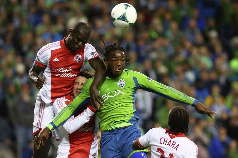Seattle Sounders player Shalrie Joseph tangles with Portland Timbers players Ben Zemanski and Pa Modou Kah, left, during an MLS playoff match between the two Pacific Northwest rivals. The Sounders fell to the Timbers 2-1.  Photo: JOSHUA TRUJILLO, SEATTLEPI.COM / SEATTLEPI.COM
