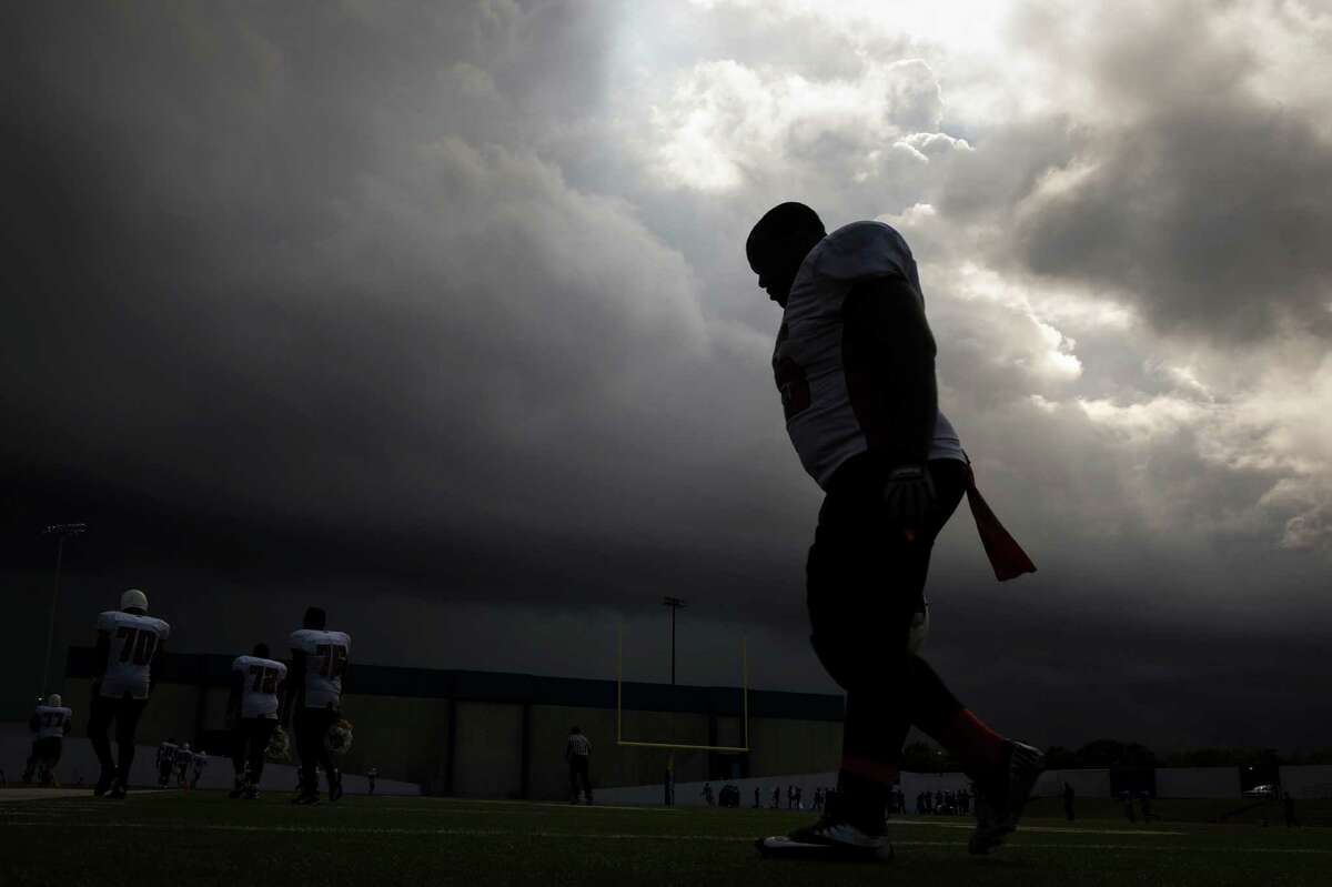 As dark storm clouds roll over the stadium Scarborough lineman Kelderick Suazo heads for the locker room at halftime of a football game against Sterling at Barnett Stadium. ( Smiley N. Pool / Houston Chronicle )