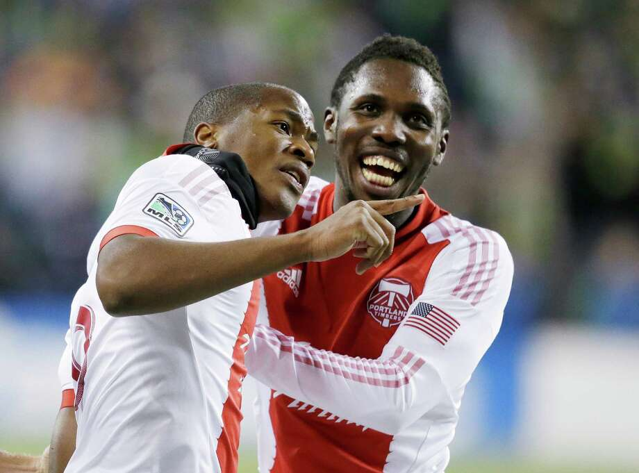 Portland Timbers' Darlington Nagbe, left, celebrates with Kalif Alhassan after scoring on an assist from Alhassan against the Seattle Sounders in the second half of the first game of the Western Conference semifinals in the MLS Cup soccer playoffs. Photo: ELAINE THOMPSON, TED S. WARREN / TED S. WARREN