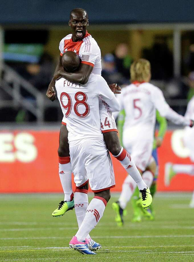 Portland Timbers' Pa Modou Kah, top, celebrates with  teammate Mamadou Danso (98) after Timbers' Darlington Nagbe scored a goal in the second half of the first game of the Western Conference semifinals against the Seattle Sounders in the MLS Cup soccer playoffs on Saturday, Nov. 2, 2013, in Seattle. The Timbers defeated the Sounders 2-1 in the first of two aggregate-score matches. (AP Photo/Ted S. Warren) Photo: TED S. WARREN, ASSOCIATED PRESS / ASSOCIATED PRESS