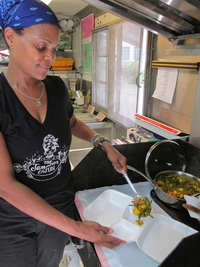 Nyjuma Howard serving up vegetable curry at the Jamaican Cajun food truck. Photo: Cat5