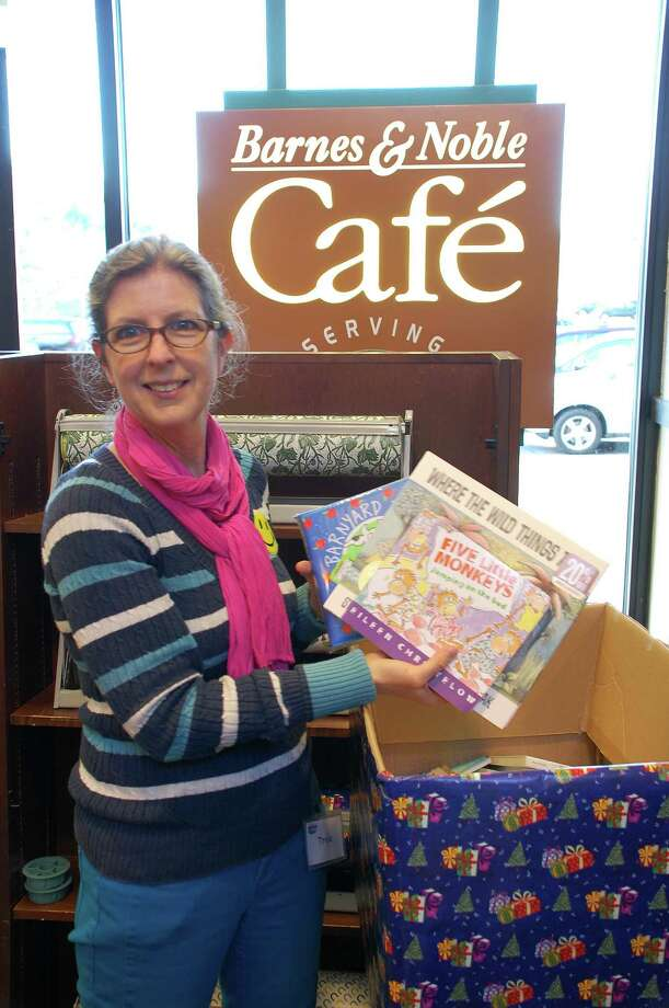 Tricia Tierney, community relations manager for Barnes & Noble in Westport, shows books being collected at the store for donation to groups that will distribute them to children in the region. Photo: Jarret Liotta / Westport News contributed