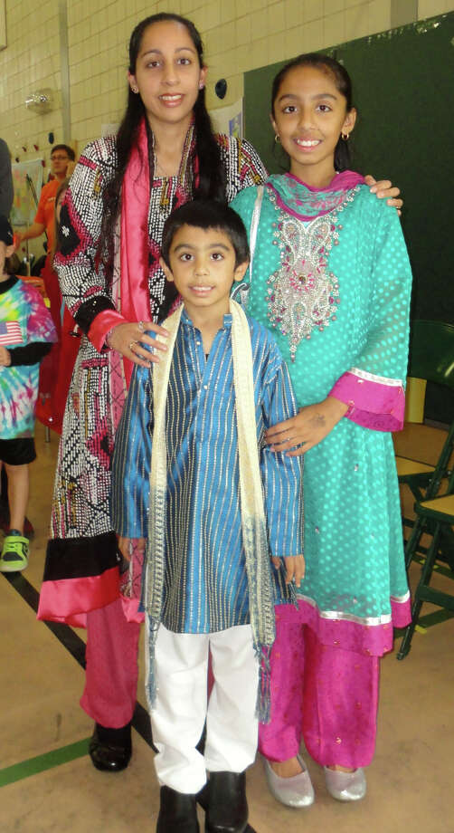Among the hundreds of people who attended the McKinley School World's Fair on Saturday were Sadaf Mohammad, her daughter Sana, 11, a student at Tomlinson Middle School, and her son Musa, a first-grader at McKinley. They are dressed in autentic Pakistani clothing called new fancy shalwar kameez, which Muslims wear for their holiday Eid. Photo: Meg Barone / Fairfield Citizen contributed