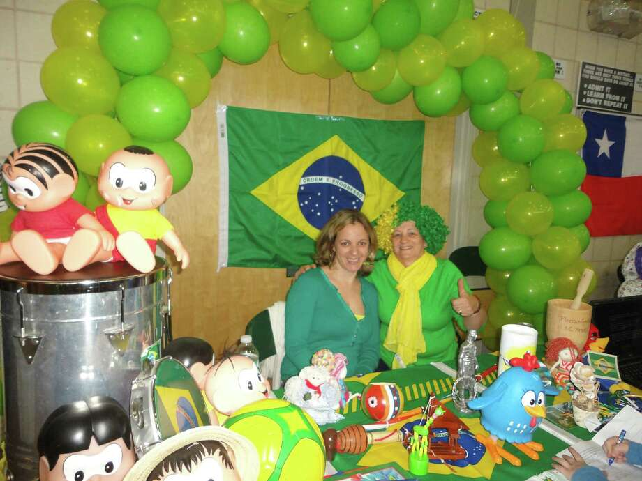 "Miriam Matos, left, and Anna Alrata staffed the booth representing the South American nation of Brazil at McKinley School's World Fair. They were surrounded by dolls and toys from Brazil. The theme of this year's fair was Toys Around the World and children were invited to collect the words for ""toy"" in the languages of the 22 nations that were represented. In Portuguese, the language in Brazil, toys are brinquedos. Photo: Meg Barone / Fairfield Citizen contributed"