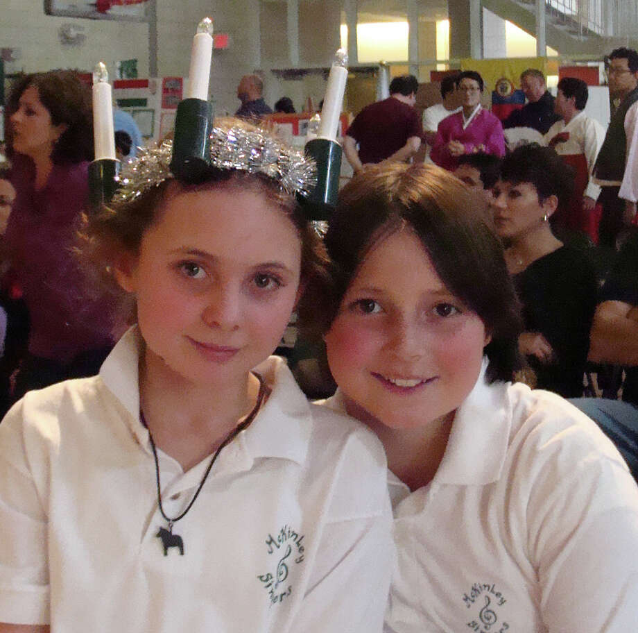 Rebecka Smith, left, 11, and Meghan Andrade, 10, participated in the World's Fair on Saturday at McKinley School. Rebecka wore a crown of candles or light, associated with Swedish observances of Christmas. Photo: Meg Barone / Fairfield Citizen contributed
