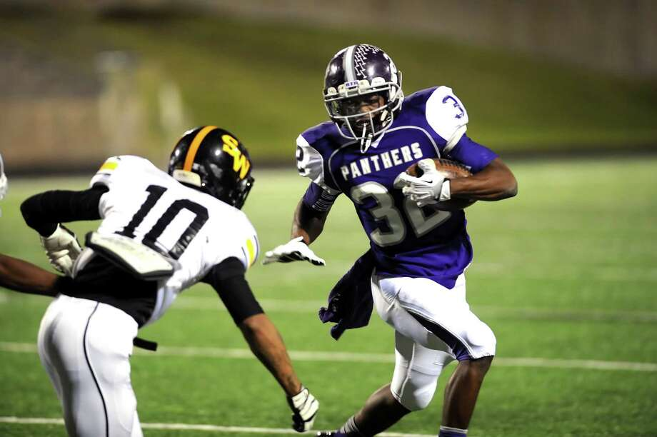 Ridge Point running back Reggie Taylor (32) uses a stiff arm to get around Spring Woods defensive back Rene Galicia (10)  during Ridge Point's 70-7 win over Spring Woods on Nov. 2 at Hall Stadium.. Photo: Eddy Matchette, For The Chronicle / Freelance