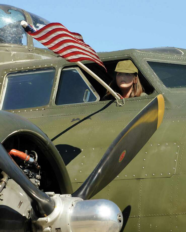 Commemorative Air Force Cadet Carolyn Bienvenu, of The Woodlands, sitting in the cockpit, unfurls the American Flag during the B-17 bomber tour and flight at the Tomball Jet Center at Hooks Airport in Spring. Visitors could tour and fly on the B-17 owned and operated by the Commemorative Air Force Gulf Coast Wing based in Houston. Photo by David Hopper Photo: David Hopper, For The Chronicle / freelance