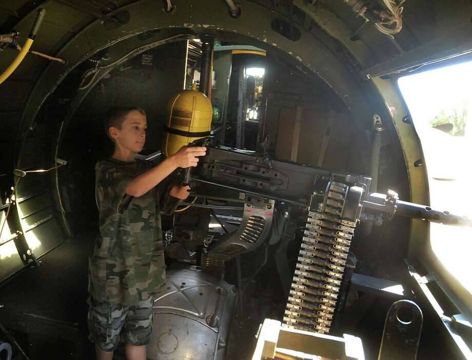 "Eleven year old Cogan Allen, of Spring 77379, ""operates"" the machine gun on the B-17 during the B-17 bomber tour and flight at the Tomball Jet Center at Hooks Airport in Spring. Visitors could tour and fly on the B-17 owned and operated by the Commemorative Air Force Gulf Coast Wing based in Houston. Photo by David Hopper Photo: David Hopper, For The Chronicle / freelance"