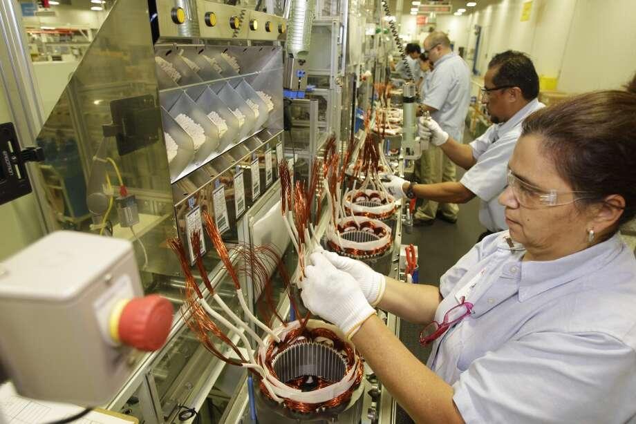 Toshiba employees Jenny Alecio and Jesus Vallejo work on a hybrid car motor stator assembly line at Toshiba, 13131 West Little York Road, Wednesday, Oct. 9, 2013, in Houston. Photo: Melissa Phillip, Houston Chronicle