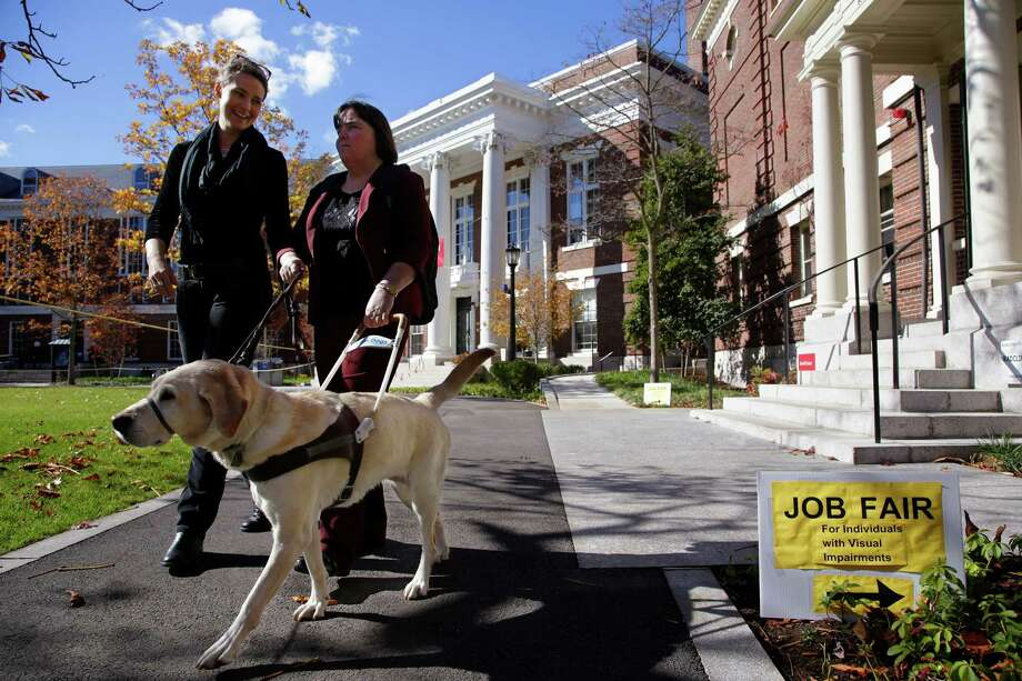 "Marie Hennessy, president of the Perkins School for the Blind alumni association leaves a job fair for the visually impaired with her guide dog ""Azalea"" and a volunteer guide, left, on the Radcliffe Yard campus in Cambridge, Mass., Thursday, Oct. 24, 2013. Despite technological advances that dramatically boost their capabilities, blind people remain largely unwanted in U.S. workplaces where about 24 percent of working-age Americans with visual disabilities hold full-time jobs. Photo: Stephan Savoia, AP / AP"