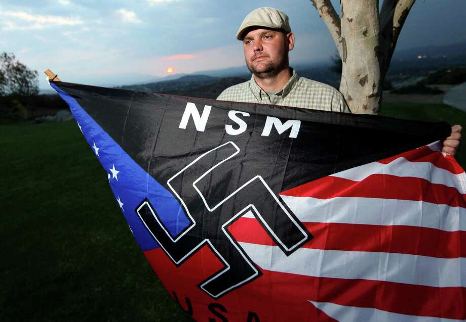 FILE - In this Oct. 22, 2010 file photo, Jeffrey Hall, who was killed by his then-10-year-old son, holds a neo-Nazi flag while standing at Sycamore Highlands Park near his home in Riverside, Calif. A California judge ruled Thursday, Oct. 31, 2013, that the boy, now 13, will spend at least the next seven years in a state juvenile facility. Judge Jean R. Leonard said the maximum the boy can serve would be until he is 23. He'll be eligible for parole in seven years. The decision came after prosecutors and defense attorneys argued for months about the best placement to assure his safety and rehabilitation. Photo: Sandy Huffaker, AP / AP2010