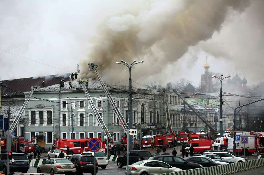 Fire fighters work at the site of a fire at the building of the School of Modern Drama theater in Moscow, Russia, Sunday, Nov. 3, 2013. The fire broke out in the attic of the building and more than 350 people were evacuated. Photo: Mikhail Listopadov, AP / AP2013