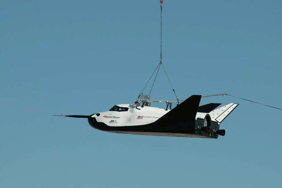 In this Aug. 22, 2013 photo made available by NASA, the Sierra Nevada Corporation's Dream Chaser spacecraft is carried by a helicopter during a test in Sparks, Nev. On Saturday, Oct. 26, 2013, the Nevada-based company tested a full-scale model at Edwards Air Force Base in California in its first free flight, but after being dropped by a helicopter, the left landing gear deployed too late and the test vehicle skidded off the runway. Photo: Carla Thomas, AP / NASA2013
