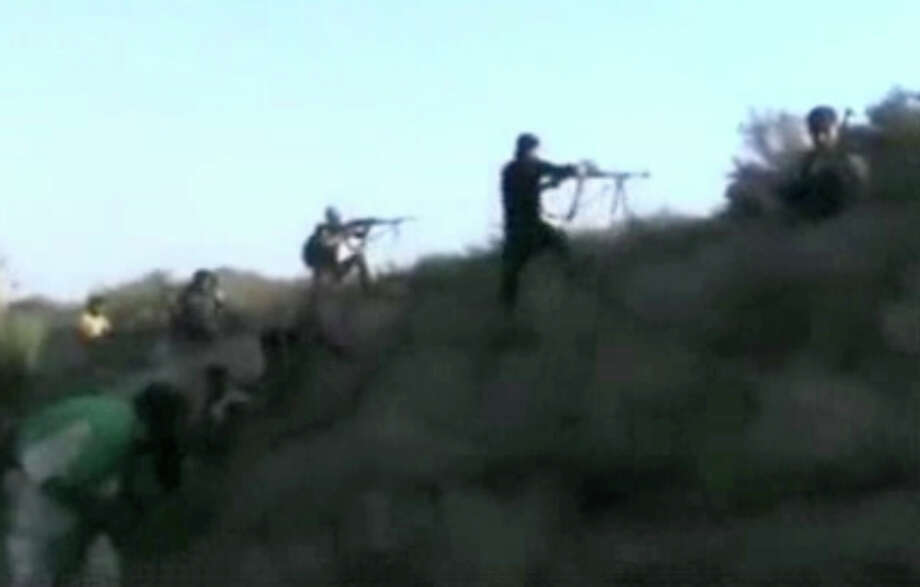 This image made from citizen journalist video posted by the Shaam News Network, which is consistent with other AP reporting, Syrian rebels fire at government forces at a military airport in Deir el-Zour, Syria, Monday, Oct. 28, 2013. The fighting coincided with the first visit to Syria by the U.N.-Arab League envoy Lakhdar Brahimi in almost a year. Photo: Uncredited, AP / AP2013