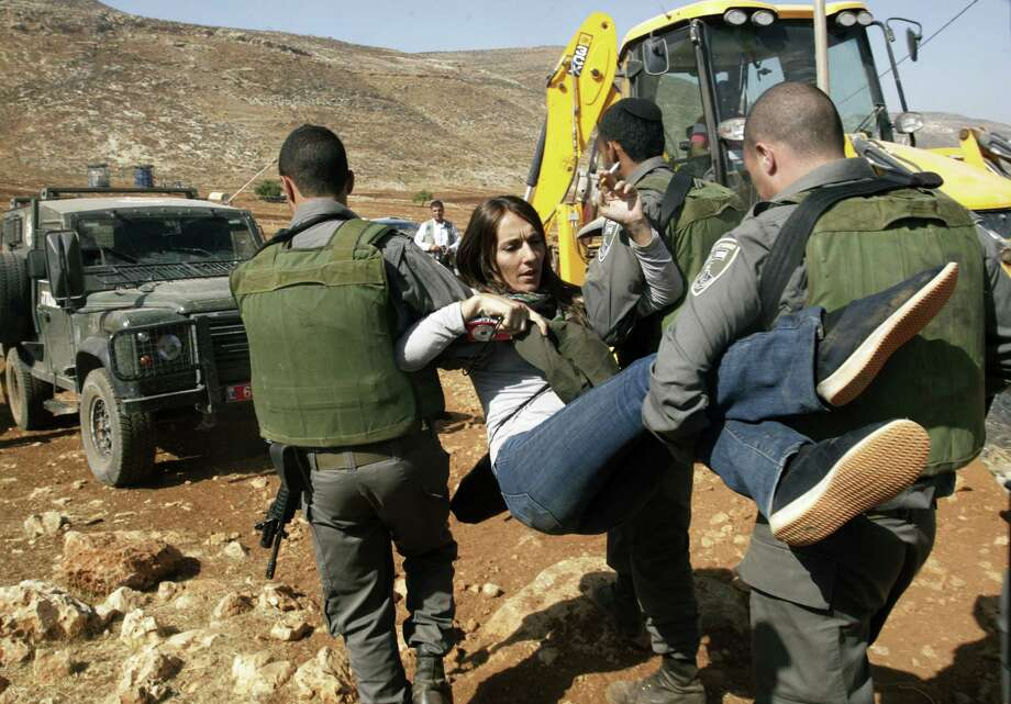 Israeli border police officers remove a foreign activist from the scene of Israeli military's demolition of tin shacks, animal shelters, tents and water wells in Aqraba village, near the settlement of Itamar, Nablus, West Bank, Tuesday, Oct. 29, 2013. The Israeli military said it demolished four structures that had been built illegally in the village. Photo: Nasser Ishtayeh, AP / AP2013