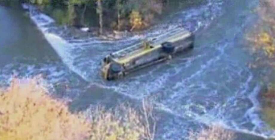 This image provided by KAKE-TV shows a school bus after it toppled into a creek, Thursday, Oct. 31, 2013 in Douglass, Kan. Ten Kansas children and a school bus driver were pulled to safety from a fast-moving creek Thursday after the bus toppled into the water and landed half-submerged on its side. (AP Photo/KAKE-TV) Photo: Uncredited, AP / AP2013