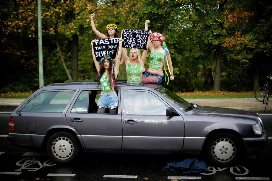 "Femen activists protest against a ban on women driving in Saudi Arabia in front of the Saudi Arabian Embassy in Berlin, Monday, Oct. 28, 2013. Though no laws ban women from driving in Saudi Arabia, authorities do not issue them licenses. Slogan painted activist at second right reads, ""we steer now"". Photo: Markus Schreiber, AP / AP2013"