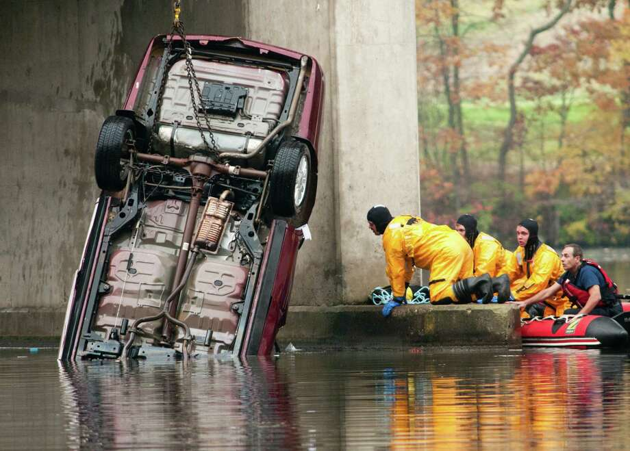 Emergency responders try to locate the victim in a car that crashed from Interstate 96 into the Thornapple River in Cascade Twp. Wednesday, Oct. 30, 2013. Police say the driver is dead after the vehicle veered off the interstate and crashed into the river. Photo: Chris Clark, AP / The Press, MLive.com
