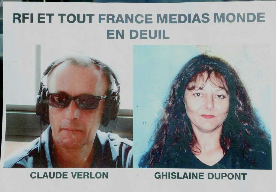 "Pictures of French RFI journalists, Ghislaine Dupont, right, and Claude Verlon on a poster headed ""RFI and all France Media World in Mourning"" displayed in a window in Paris, Sunday, Nov. 3, 2013. The two French RFI journalists were abducted and killed Saturday after an interview with a rebel leader in the town of Kidal, northern Mali, which remains under the de facto control of rebels despite the presence of French and U.N. troops. Photo: Jacques Brinon, AP / AP"