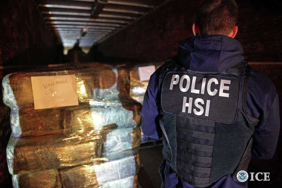 This Oct. 31, 2013 photo provided by U.S. Immigration and Customs Enforcement shows agents with bales of some of more than eight tons of marijuana and cocaine seized from a tunnel designed to smuggle drugs from Tijuana, Mexico, to San Diego.  The tunnel links warehouses in Tijuana and San Diego's Otay Mesa industrial area. Photo: Paul Caffrey, AP / PUBLIC DOMAIN2013