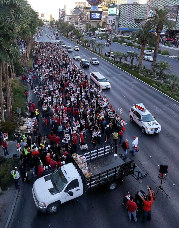 Hundreds of Culinary Workers Union members picket outside the Cosmopolitan of Las Vegas casino, Friday, Nov. 1, 2013, in Las Vegas.  More than 100 members of the union were arrested after staging a sit-in inside the casino lobby while demonstrating against the casino and its owner Deutsche Bank over a contract dispute involving  wages, health care and job security. Photo: Julie Jacobson, AP / AP