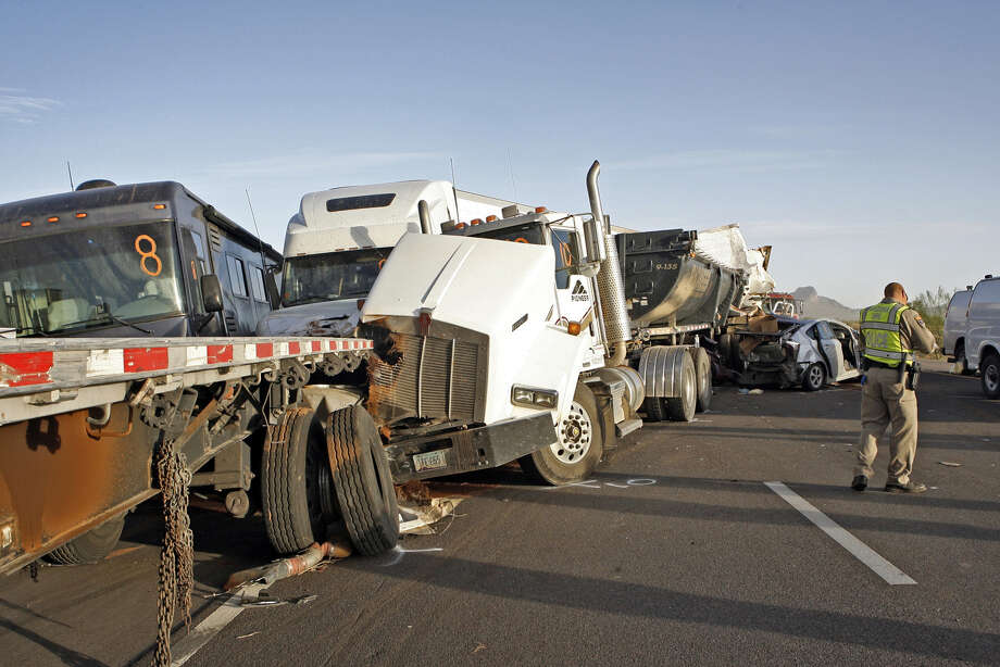 Arizona Department of Public Safety officers investigate a multiple fatality accident involving six semi tractor-trailers and 19 other vehicles in the eastbound lanes of Interstate 10 south of Casa Grande, Ariz., on Tuesday, Oct. 29, 2013.  Authorities say three people are dead and at least 12 others injured after a dust storm led to chain-reaction collisions. (AP Photo/Arizona Daily Star, Ron Medvescek)  Photo: Ron Medvescek, AP / AP2013