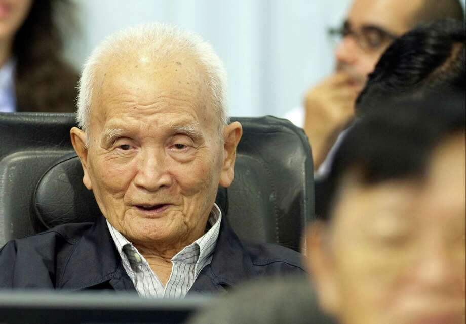 In this photo released by the Extraordinary Chambers in the Courts of Cambodia, Nuon Chea, left, who was the Khmer Rouge's chief ideologist and No. 2 leader, waits before his final statements at the U.N.-backed war crimes tribunal in Phnom Penh, Cambodia, Thursday, Oct. 31, 2013. Former Khmer Rouge leader Nuon Chea has denied all charges against him on the last day of a trial for leaders of the Cambodian regime widely blamed for the deaths of some 1.7 million people. Photo: Mark Peters, AP / AP2013