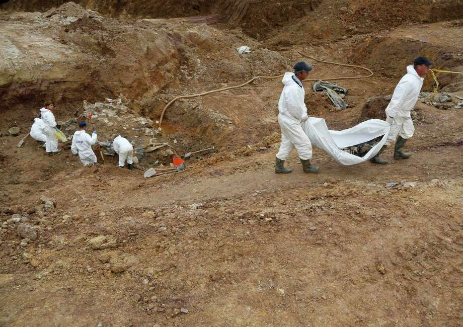 Forensic experts, members of the International Commission on Missing Persons (ICMP), and Bosnian workers search for human remains at a mass grave in the village of Tomasica, near the Bosnian town of Prijedor, 260 kms north west of Sarajevo, on Thursday, Oct. 31, 2013. Forensic experts have unearthed the 360 body  remains so far , but believe there are many more yet undiscovered as they excavate a 7 meters deep trench to find the remains of Bosniaks and Croats killed by Serb forces during their campaign to eliminate all non-Serbs from parts of the country they controlled during the 1992-95 Bosnian war. Authorities are still searching for 1,200 Bosniaks and Croats missing from the area of Prijedor. Photo: Amel Emric, AP / AP