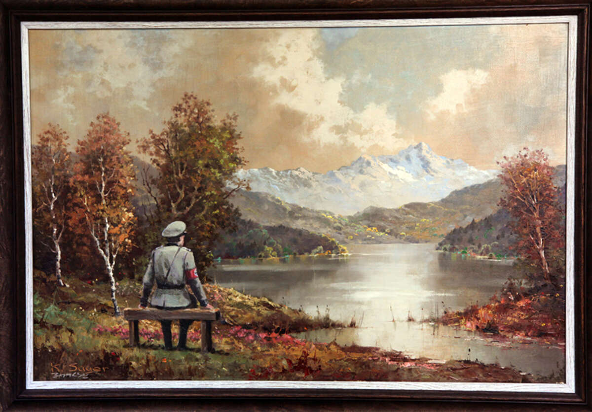 This undated file photo provided by Housing Works shows a painting, which includes an addition to the scene by the secretive British graffiti artist Banksy. The painting was auctioned off Thursday, Oct. 31, 2013, for $615,000. The original painting first sold for $50 at a Manhattan thrift shop that benefits Housing Works, an organization that fights homelessness and AIDS. Banksy added a Nazi soldier to the landscape scene and Housing Works sold it in an online auction.