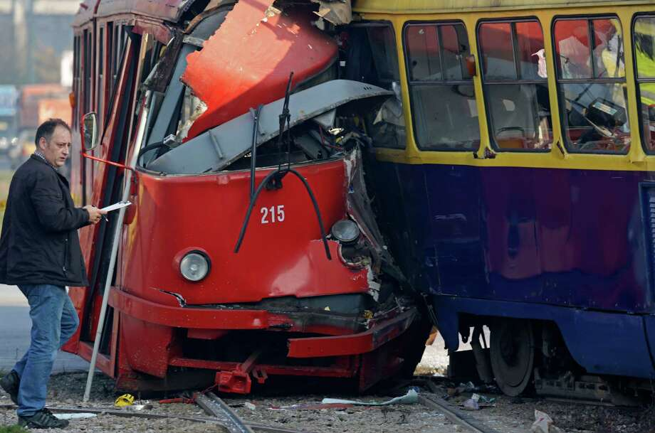 Police officers investigate the crash site of two trams in the Bosnian capital of Sarajevo, on Friday, Nov. 1, 2013. Authorities say some 45 people were injured when one tram slammed into another at a busy downtown intersection in Sarajevo. Irfan Nefic, the spokesman for the Sarajevo police, said Friday court experts are still investigating the causes of the accident. He said so far none of the injuries of the approximately 45 people were life threatening. Photo: Amel Emric, AP / AP