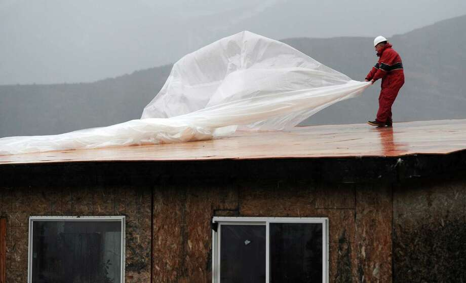 "Ken Schacht braves driving rain to replace plastic sheeting protecting a home under construction on Monday, Oct. 28, 2013, along Carl Street in Bear Valley in Anchorage, Alaska. A sheet had been in place to keep water out at the project, but ""the wind just shredded it,"" he said, causing some flooding. Wind gusts as high as 106 mph were reported at Bear Valley early Monday morning, according to Dave Stricklan, a meteorologist with the National Weather Service. Photo: Erik Hill, AP / Anchorage Daily News"