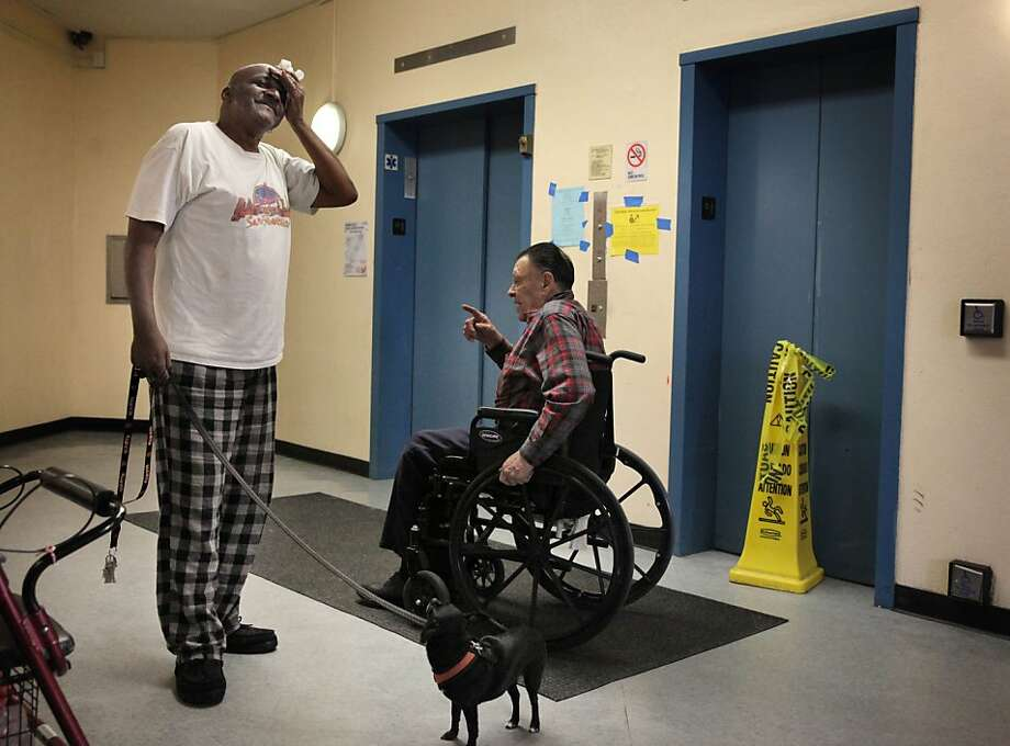Clementina Towers residents Michael Dismuke (left) and Salomon Lopez chat next to their broken elevator. Photo: Lea Suzuki, The Chronicle