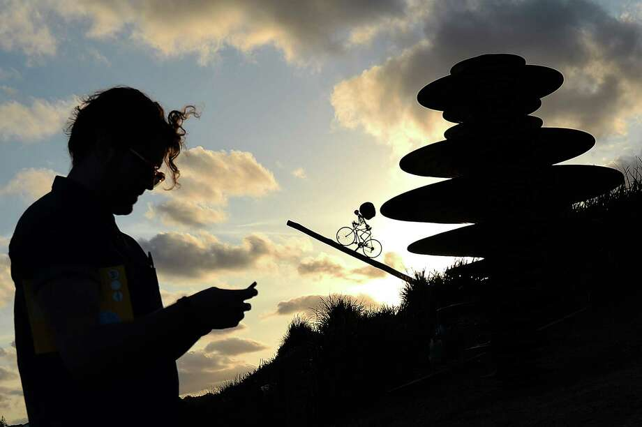 A visitor prepares his mobile phone to take picture of sculptures which are part of the Sculpture by the Sea exhibition which runs along the Bondi to Tamarama coastal walk in Sydney, on October 31, 2013. The world's largest annual free-to-the-public outdoor sculpture exhibition runs 24 October - 10 November 2013 and features over 100 sculptures by artists from Australia and around the world. AFP PHOTO / Saeed Khan Photo: SAEED KHAN, Getty Images / 2013 AFP