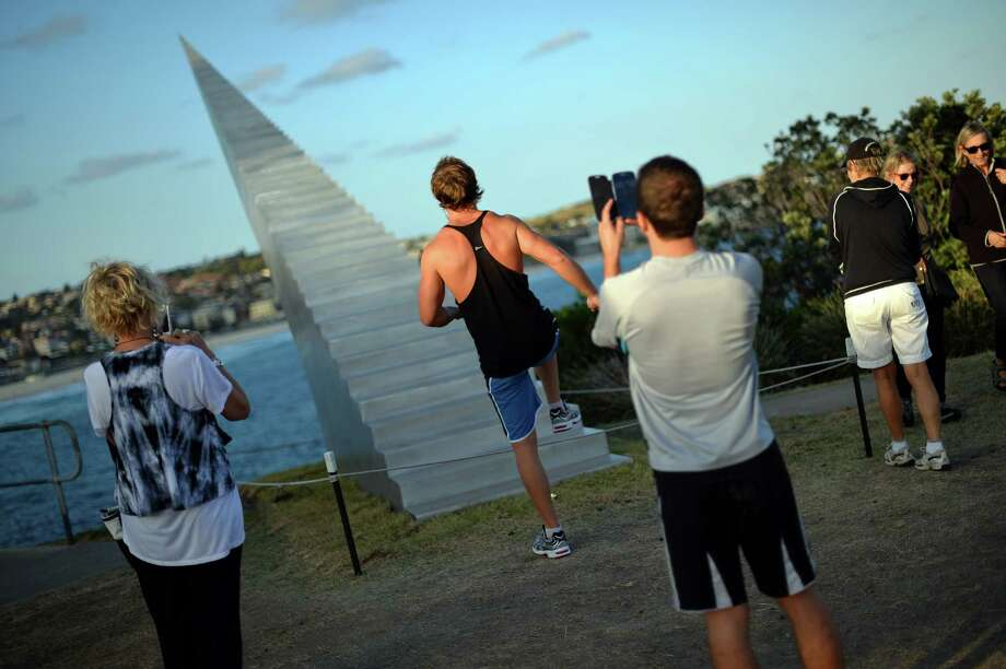 A visitor poses next to a sculpture, which is part of the Sculpture by the Sea exhibition which runs along the Bondi to Tamarama coastal walk in Sydney, on October 31, 2013. The world's largest annual free-to-the-public outdoor sculpture exhibition runs 24 October - 10 November 2013 and features over 100 sculptures by artists from Australia and around the world. AFP PHOTO / Saeed Khan  Photo: SAEED KHAN, Getty Images / 2013 AFP