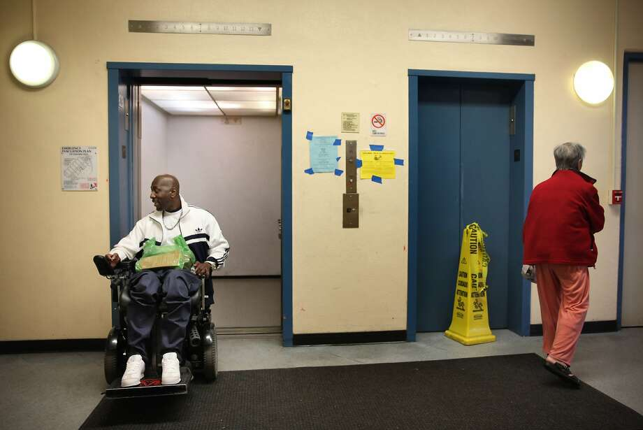 Clementina Towers resident Jamel Burrell makes his way into a working elevator next to a broken one as he heads to his apartment. Photo: Lea Suzuki, The Chronicle