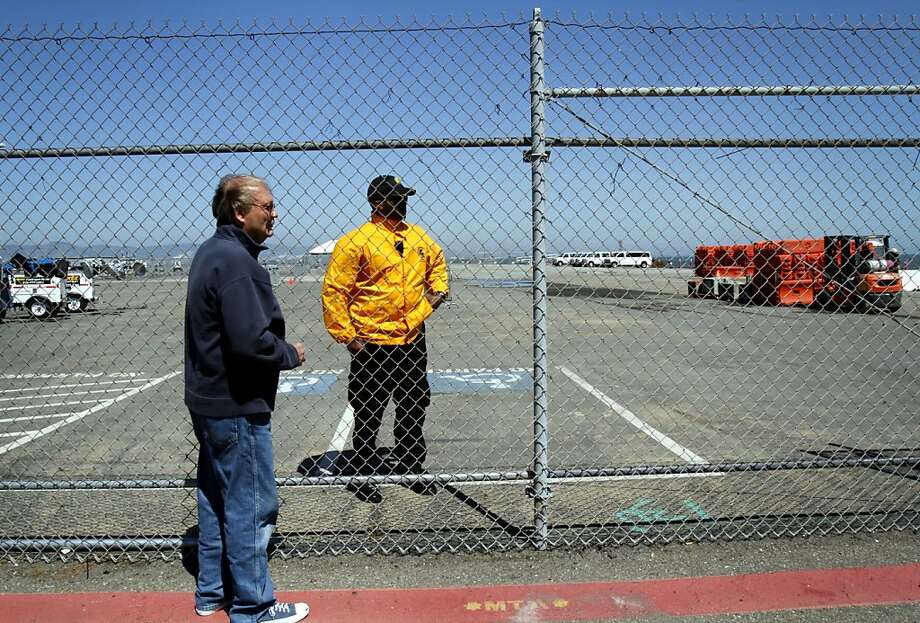Lawrence Stokus (left) stops to talk to a security guard at Piers 30-32 about the proposed waterfront arena. Stokus lives nearby and would rather see the land be used as a park. Photo: Sarah Rice, Special To The Chronicle
